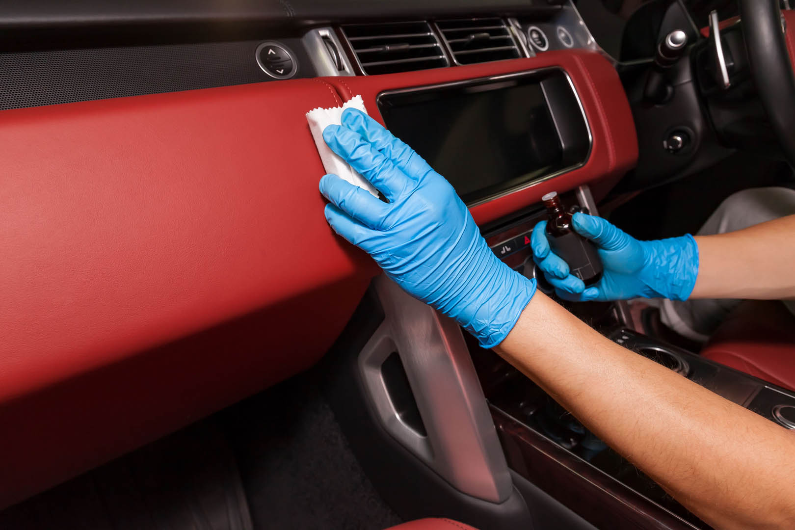 Cleaning and auto detailing services on dashboard of car with red interior